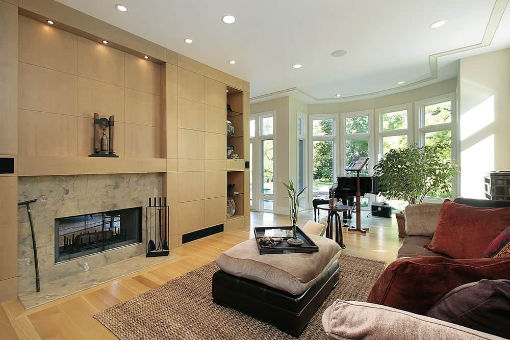 This formal living space features hardwood flooring and a brown fireplace with built-in shelving on the side. The large brown comfy couch is set in front of the fireplace.