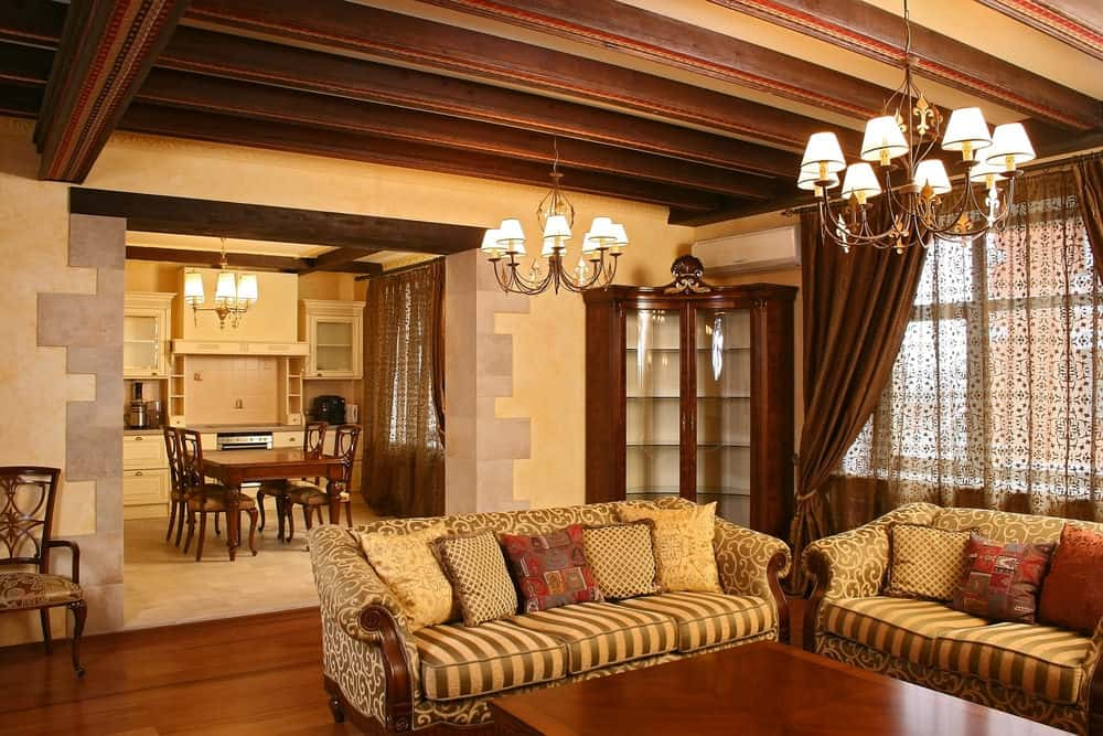 This living room features a set of classy seats and a wooden center table matching the home's hardwood flooring. The area is lighted by gorgeous chandeliers.