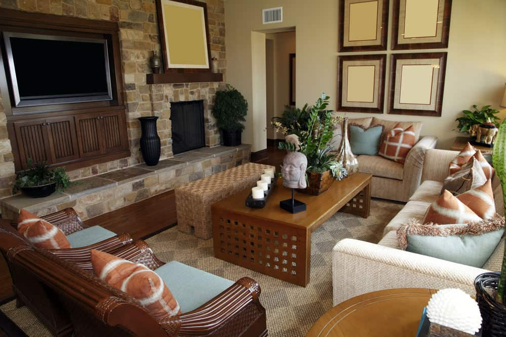 A focused shot at this family living room's set of classy seats along with a stylish wooden center table. There's a widescreen TV set in front, beside the stone fireplace.