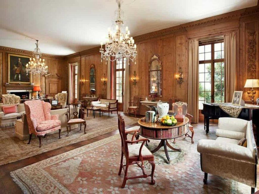 Large formal living room with brown wooden walls and hardwood floors. The are two sofa sets, the other one has an elegant center table and a piano on the side while the other one is set in front of the fireplace. The room is lighted by two glamorous chandeliers.