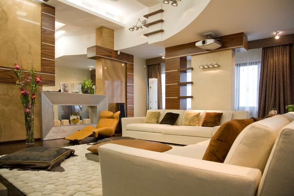 Large contemporary living room featuring a white sofa set and a large modern fireplace, along with a custom ceiling and walls.