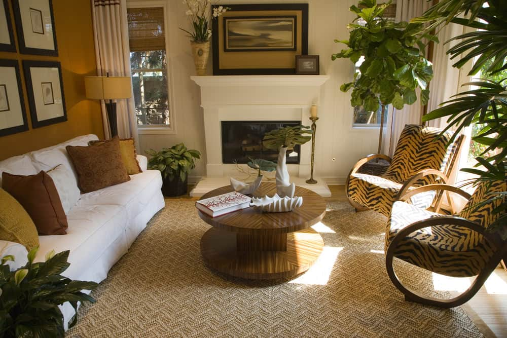 Large formal living room featuring a white couch and a round center table set on a stylish brown rug. The room is surrounded by brown walls. It also has a fireplace.