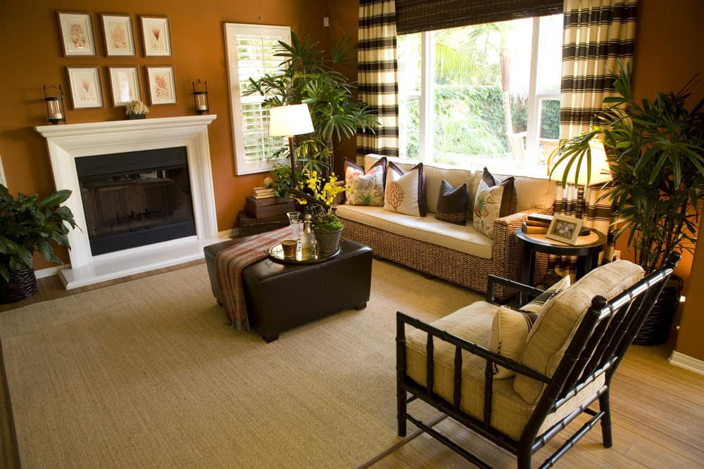 This formal living room features a rattan-framed couch and a large fireplace, along with a center table set on the brown area rug. The room is surrounded by brown walls.