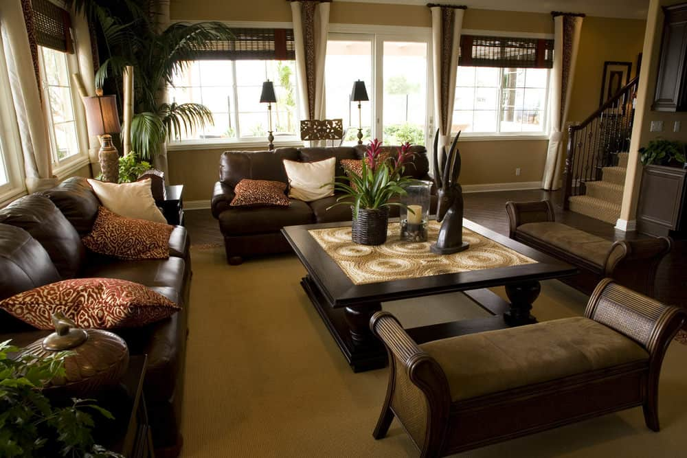 A formal living room boasting a brown leather sofa set and a large classy center table set on the room's brown area rug covering the hardwood flooring.