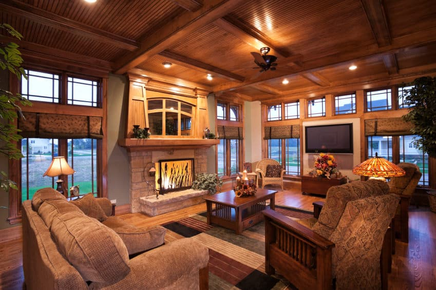 Large family living space with hardwood flooring and a wooden ceiling. It offers a cozy set of seats, a large fireplace and a widescreen TV.