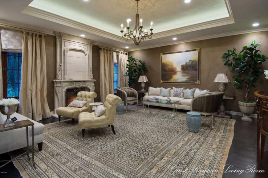 Large formal living room boasting a stunning tray ceiling and brown walls, along with hardwood flooring topped by a large stylish area rug. The room offers a set of lovely seats, along with a classy fireplace. The area is lighted by a chandelier and recessed ceiling lights.