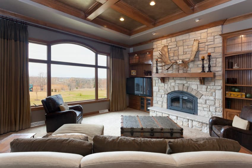 Large family living space featuring a cozy sofa set and a large stone fireplace with a widescreen TV on the side.
