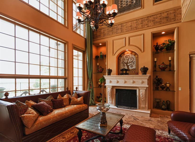 Large formal living room with brown tiles flooring and brown walls, along with a two-storey ceiling. The room offers a brown couch and a fireplace with built-in shelving on both sides.