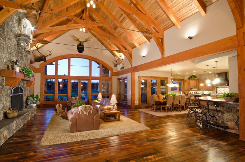 A massive great room boasting a spacious living space set under the home's tall wooden vaulted ceiling with exposed beams. The room offers a brown leather sofa set on top of a brown area rug with a large stone fireplace in front.