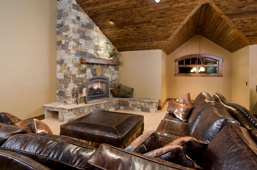 This living room features a stone fireplace along with a large brown leather sofa set.
