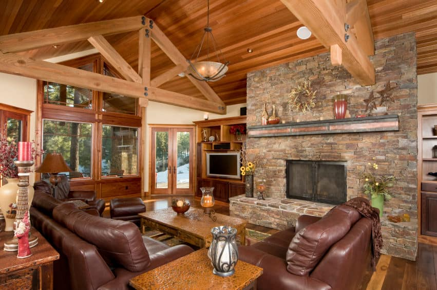 Large formal living room with hardwood flooring and a wooden vaulted ceiling with exposed beams. The room features a leather sofa set and a large stone fireplace.