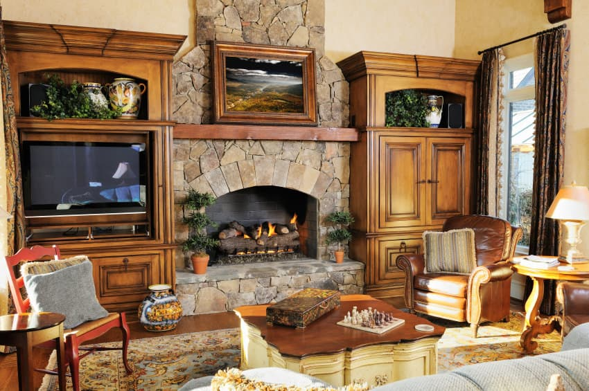 A focused shot at this family living space's large stone fireplace with a widescreen TV set beside it. The room offers classy seats and an elegant center table.