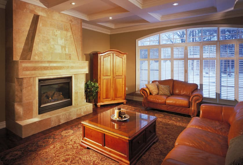 A spacious formal living room with a large fireplace and a brown leather sofa set, situated under the home's coffered ceiling and is surrounded by brown walls.