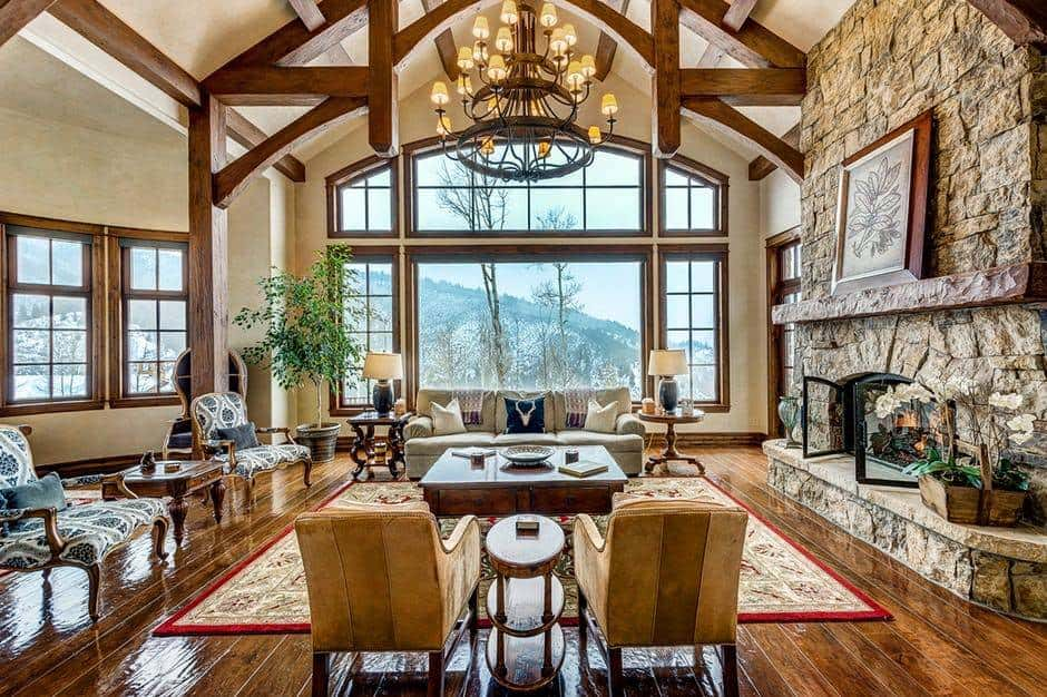 Large formal living room boasting a tall vaulted ceiling with exposed beams along with hardwood flooring. The area offers a set of classy seats and a large stone fireplace, lighted by a glamorous chandelier.