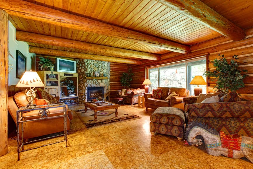 A spacious family living space featuring stunning brown flooring and a wooden ceiling with logs beams. The room offers cozy leather couches and a stone fireplace.