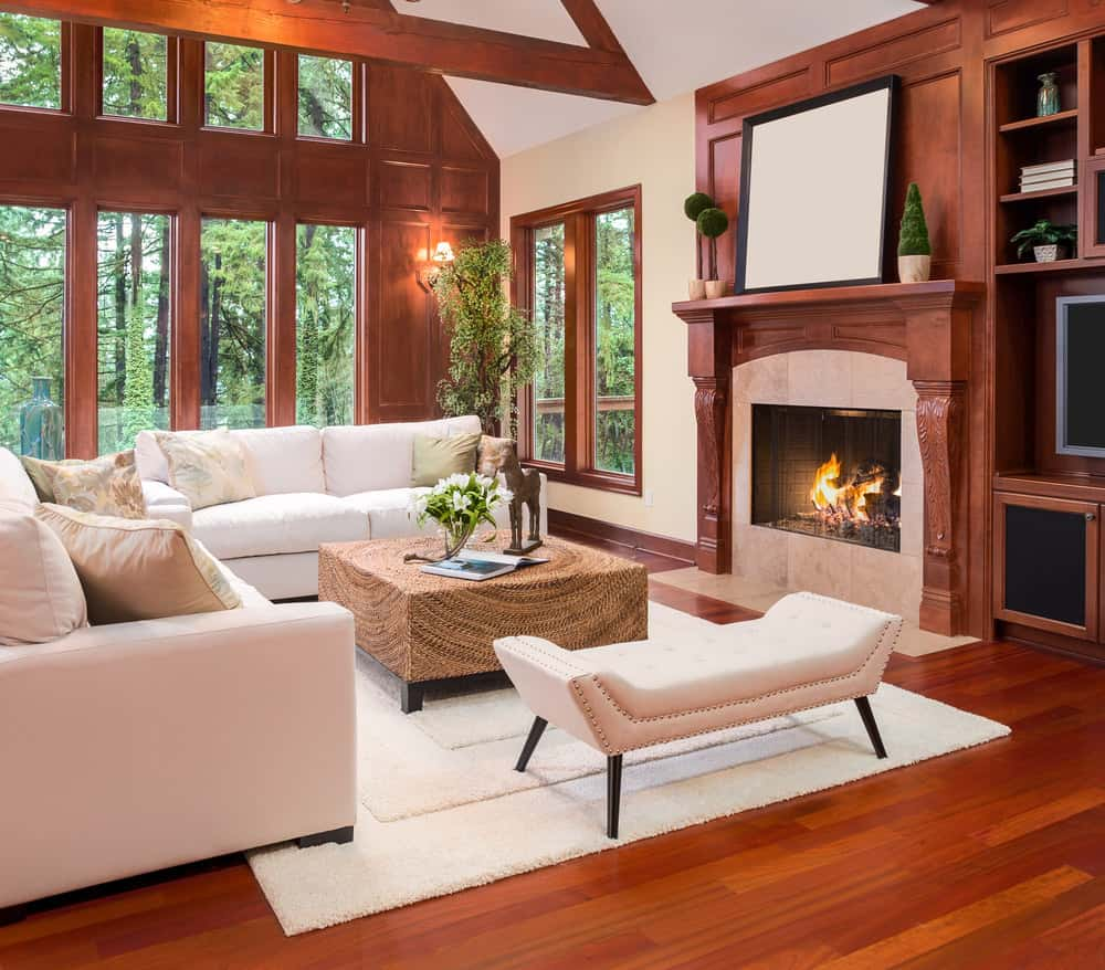 Large formal living room with a brown and white color scheme. The room offers a white sofa set with a stylish brown center table along with a fireplace.