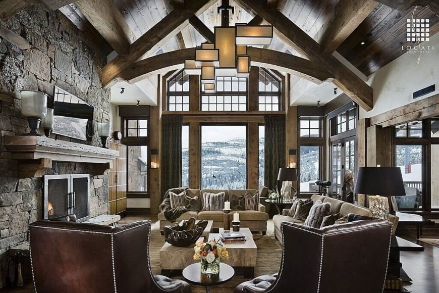 A large formal living room featuring hardwood flooring and a tall wooden ceiling with exposed beams. The room offers classy seats and a large stone fireplace.