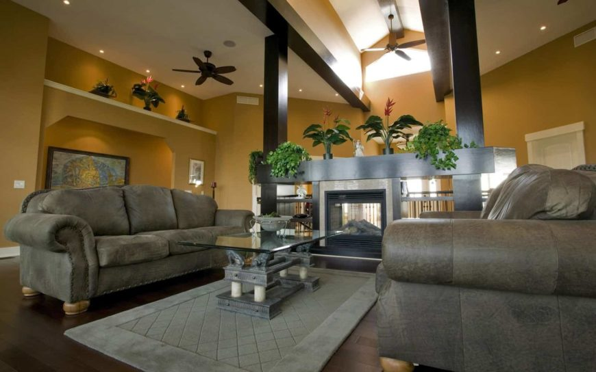 A spacious modern formal living room with elegant gray couches and a stylish glass top center table. There's a modern fireplace in the area as well.