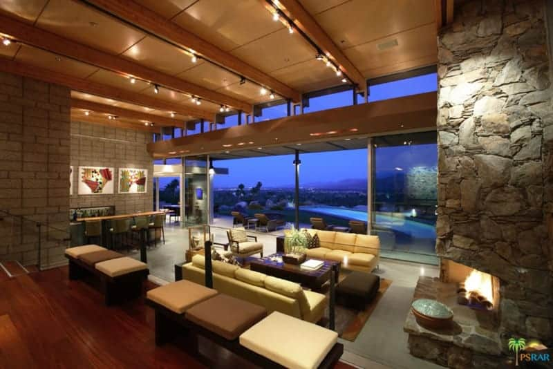 A contemporary home boasting a living space with a tall ceiling lighted by track lights. The area offers a modern and cozy sofa set along with a large fireplace.