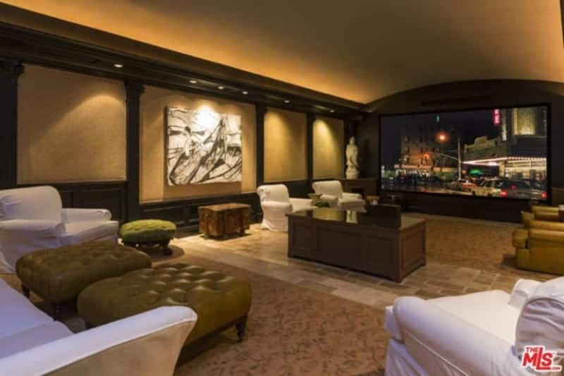Huge home-theater living space featuring a gorgeous wall design along with elegant flooring. The room offers sectional seats and a large theater-style TV in front.