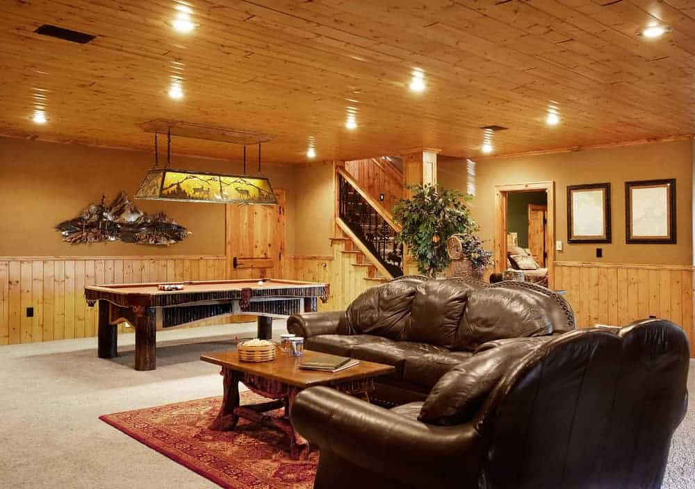 A huge family living space boasting a set of large brown sofa along with a classy wooden center table and a billiards pool set on the side.