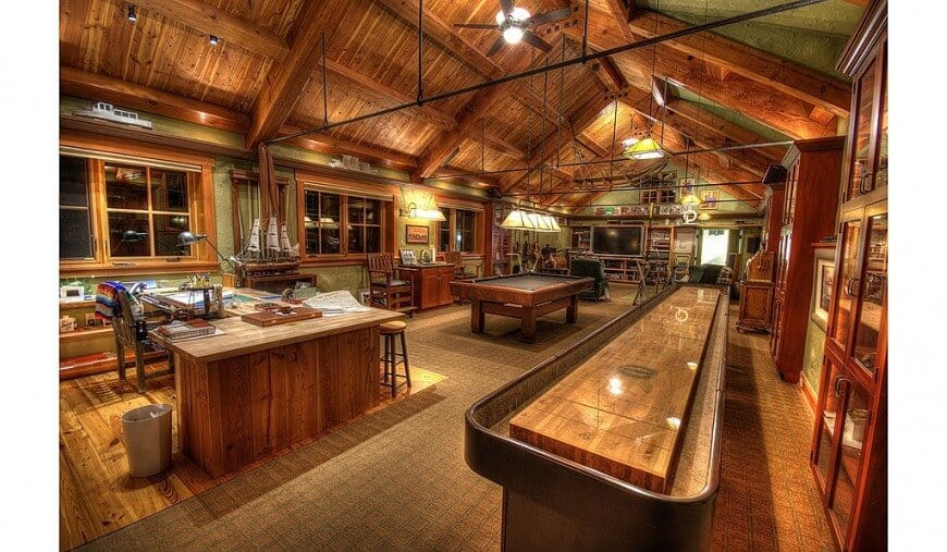 This huge room boasts a living space featuring a large TV, a billiards table at the back along with a large office desk on the other side. The room features a tall wooden vaulted ceiling with beams and green walls.