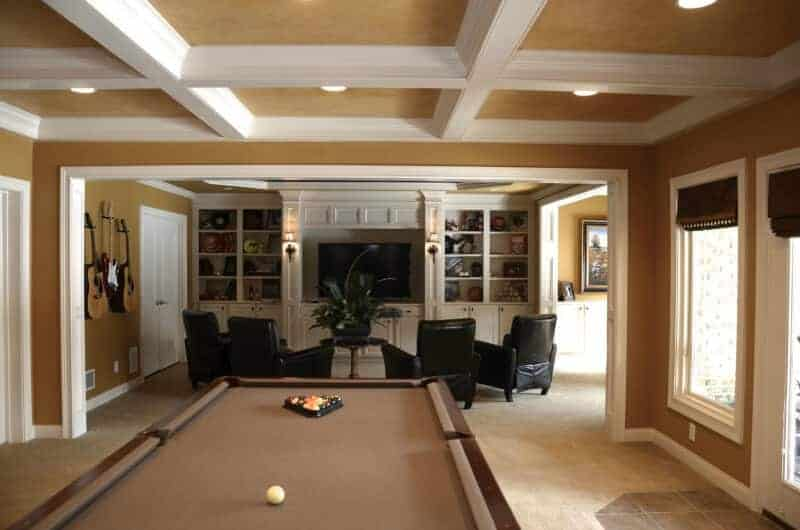 A family living space surrounded by brown walls and ceiling with a white accent. The area offers a set of black seats with a widescreen TV in front, along with a billiards table set at the back.