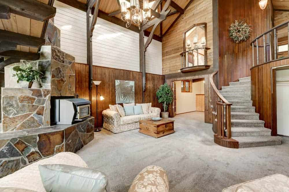 Large rustic formal living room featuring a tall wooden ceiling and gray carpet flooring. There are elegant seats along with a stylish fireplace. The area is lighted by a gorgeous chandelier.
