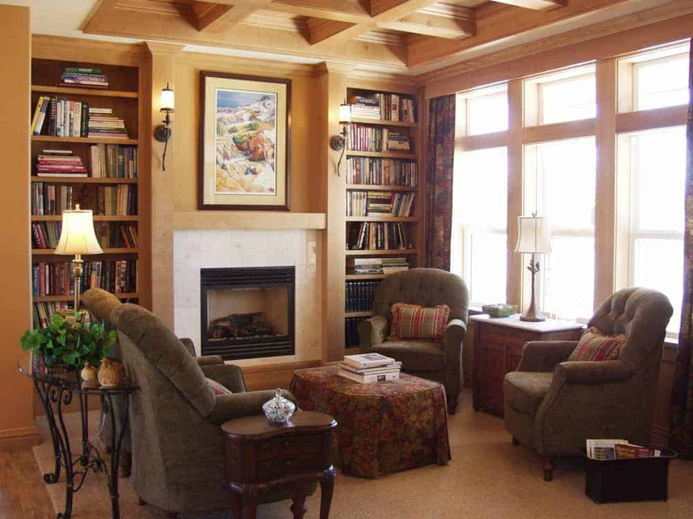A brown formal living space featuring a fireplace set in between two built-in bookshelves. The room offers a comfy set of chairs. The area has a wooden coffered ceiling.