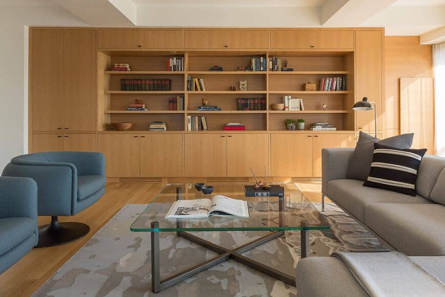 Large formal living room boasting a modern set of seats along with a glass top center table. There's a wooden built-in shelving and cabinetry on the side as well.
