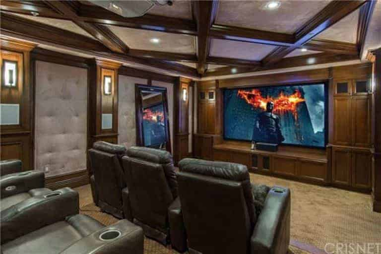 A home theater with comfy sectional seats and a stylish ceiling design, along with carpeted flooring.