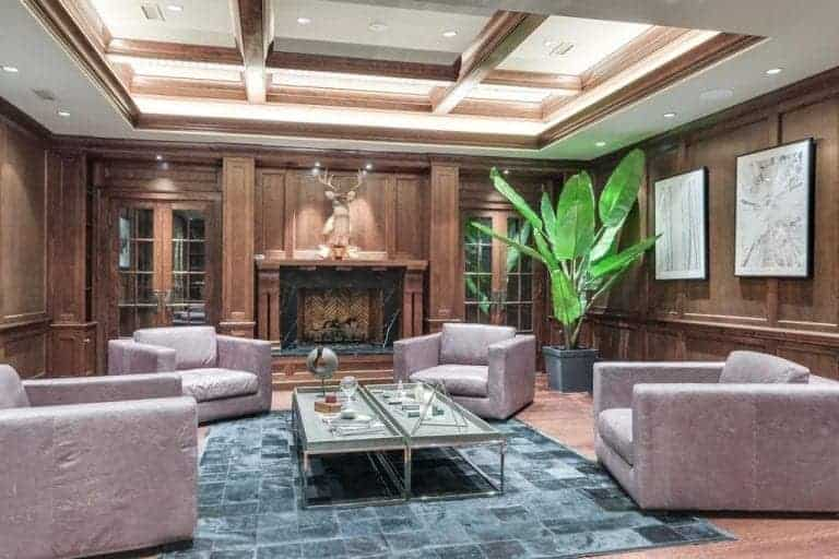 An elegant formal living room with brown wooden walls and hardwood floors, along with a beautiful coffered tray ceiling. The room offers a set of classy seats and a large fireplace.