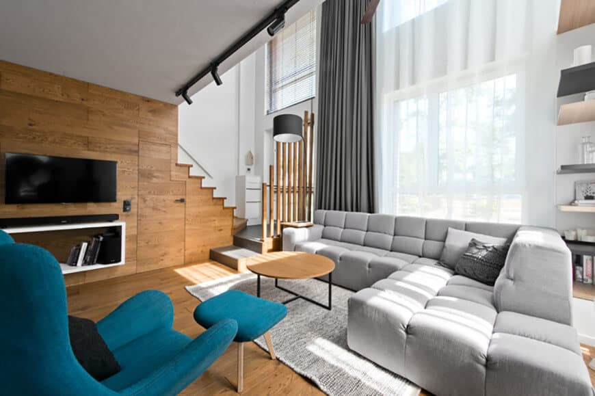 This modern living space offers a modish gray sofa set along with a blue accent chair with a footrest. There's a widescreen TV on the wooden wall as well.