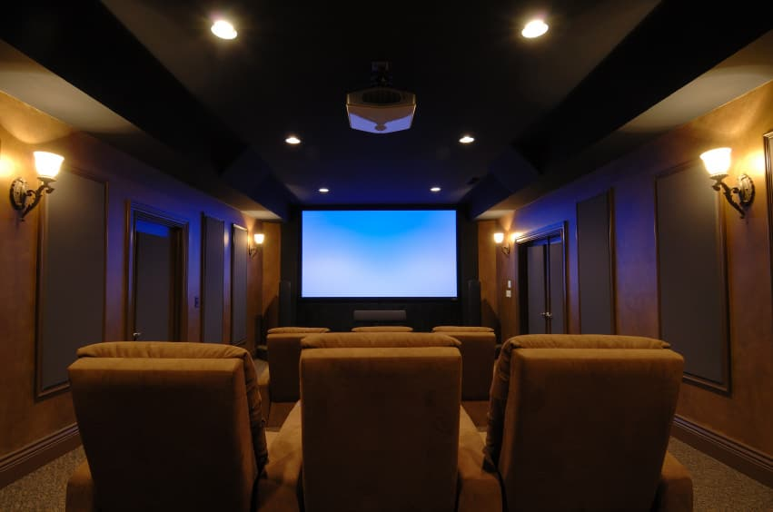 A modern home theater boasting brown walls with stylish decors and gorgeous wall lights, along with a dark ceiling lighted by lined up recessed lights. The room offers sectional seats as well.