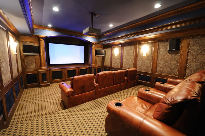 A spacious home theater with elegant walls and a gorgeous tray ceiling. The room offers a set of sectional seats set on the classy carpeted flooring.