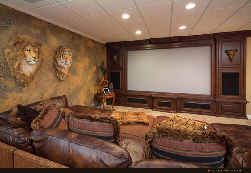 A home theater surrounded by elegantly decorated walls, along with a massive brown leather couch in front of the TV set.