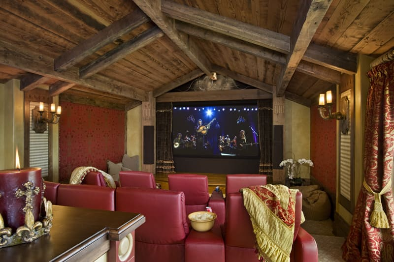 This home theater features a rustic vaulted ceiling with exposed beams. There are red sectional seats. The walls are lighted by wall lights.