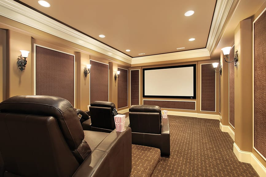 A home theater with brown walls, brown carpet flooring and a brown tray ceiling. The room is lighted by recessed and wall lights.