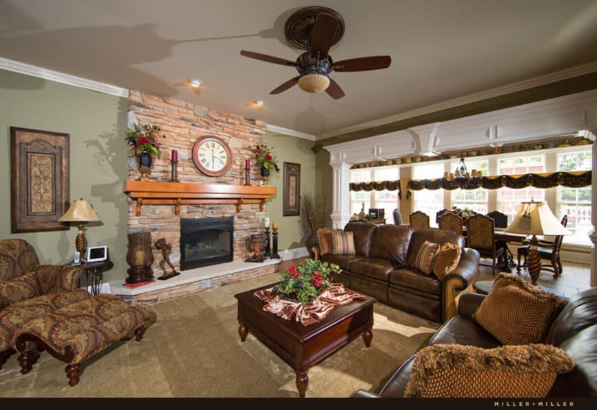 This formal living room boasts a set of gorgeous brown seats along with a fireplace, surrounded by green walls, brown carpet flooring and a regular gray ceiling.