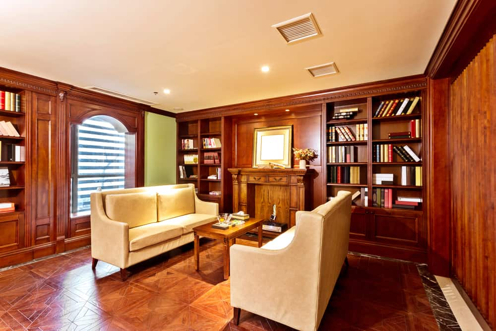 Large library living space with stunning flooring and a fireplace. The room has two classy couches surrounded by bookshelves.