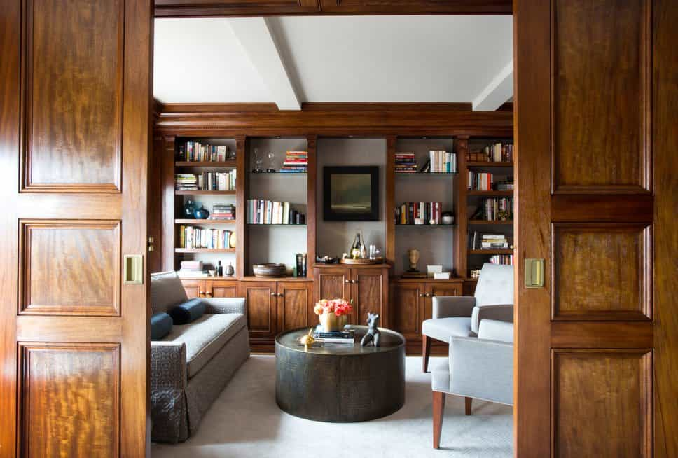 A living room with wooden sliding doors. The room offers a classy set of seats and multiple built-in shelving and cabinetry.