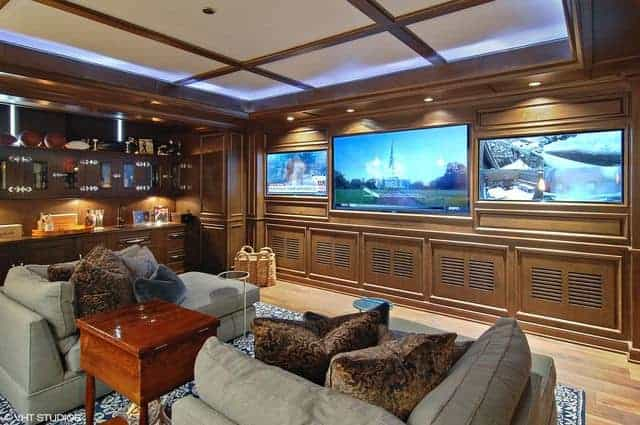 A spacious brown living space featuring a cozy sofa set on top of a stylish blue rug. There's a bar area on the side, along with a large flat-screen TV on the wall in front.