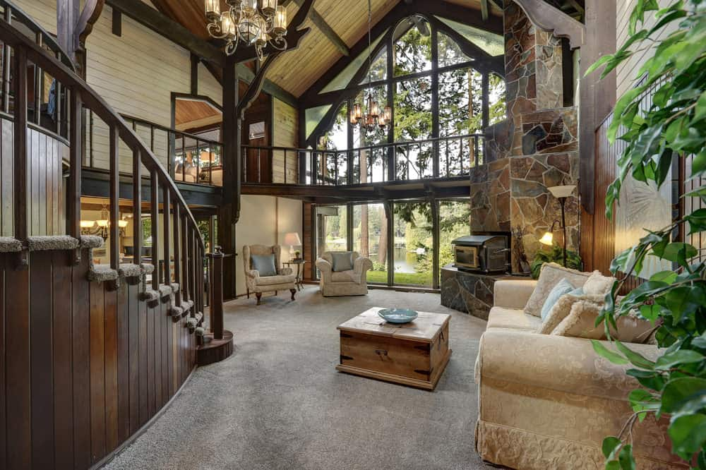 A rustic formal living room featuring a wooden vaulted ceiling along with gray carpet flooring. The room features a set of classy seats and a stone fireplace.