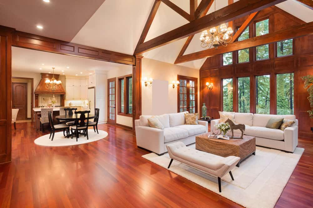 Spacious great room featuring hardwood flooring and white walls. It offers a living space with a white sofa set under the home's vaulted ceiling with exposed beams.