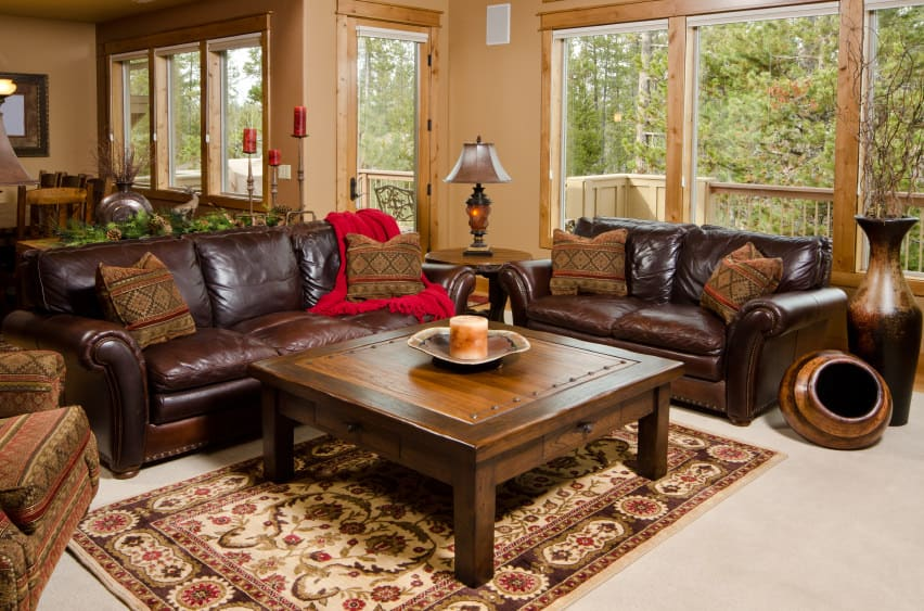 A focused look at this formal living room's brown leather seats and a stylish wooden center table set on top of the beautiful area rug on top of the carpet flooring.