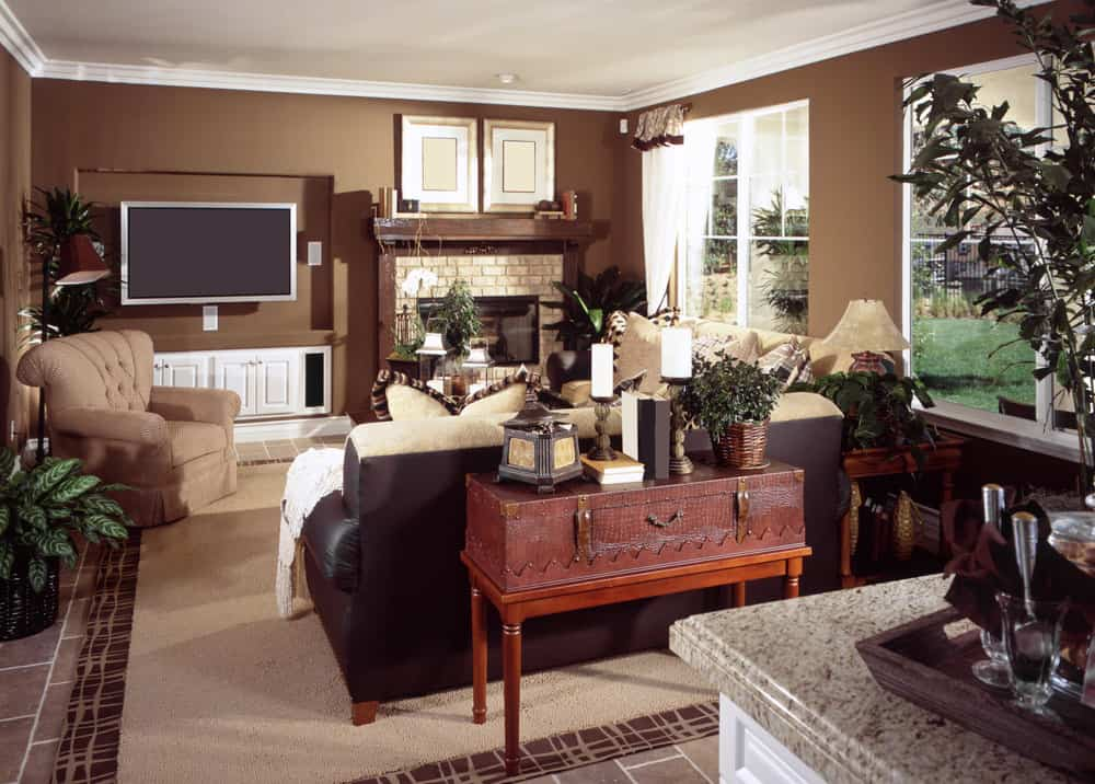 A family living space featuring brown walls and a large area rug covering the tiles flooring. The room boasts a widescreen TV on the beside the fireplace.