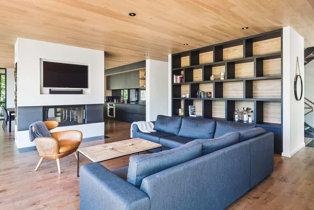 Large family living room with hardwood flooring and a wooden ceiling. It offers a stylish blue sofa set, a fireplace and a TV set in front. along with built-in shelving on the side.