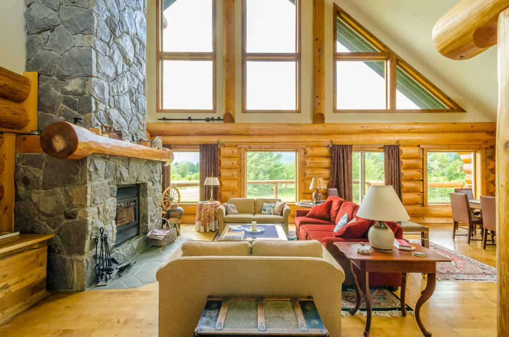 Spacious formal living room with a large stone fireplace and a cozy sofa set in front of it, set under the home's tall shed ceiling.