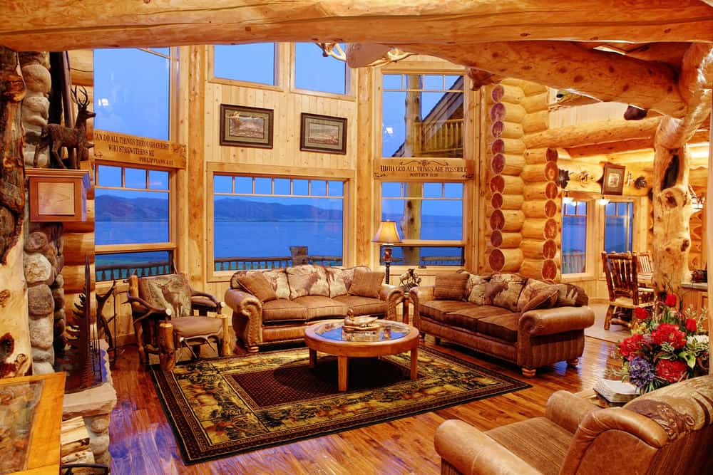 Large formal living room with logs walls and ceiling, along with hardwood flooring. It features a brown leather sofa set and a stylish area rug, along with a large fireplace.