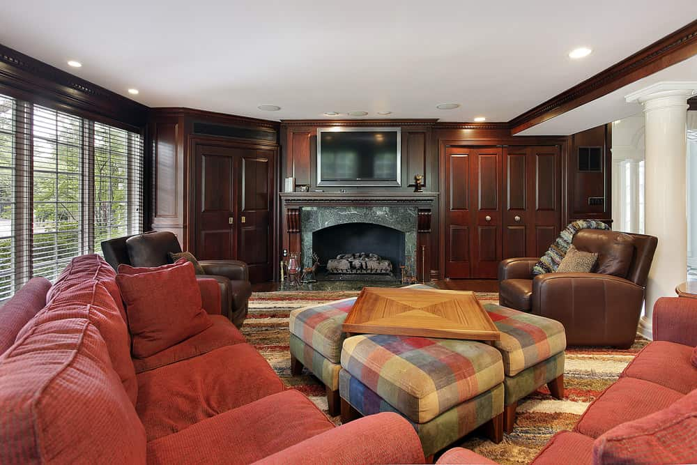 Large family living room featuring a red sofa set and a set of large ottomans. There's a fireplace and a large TV above it.